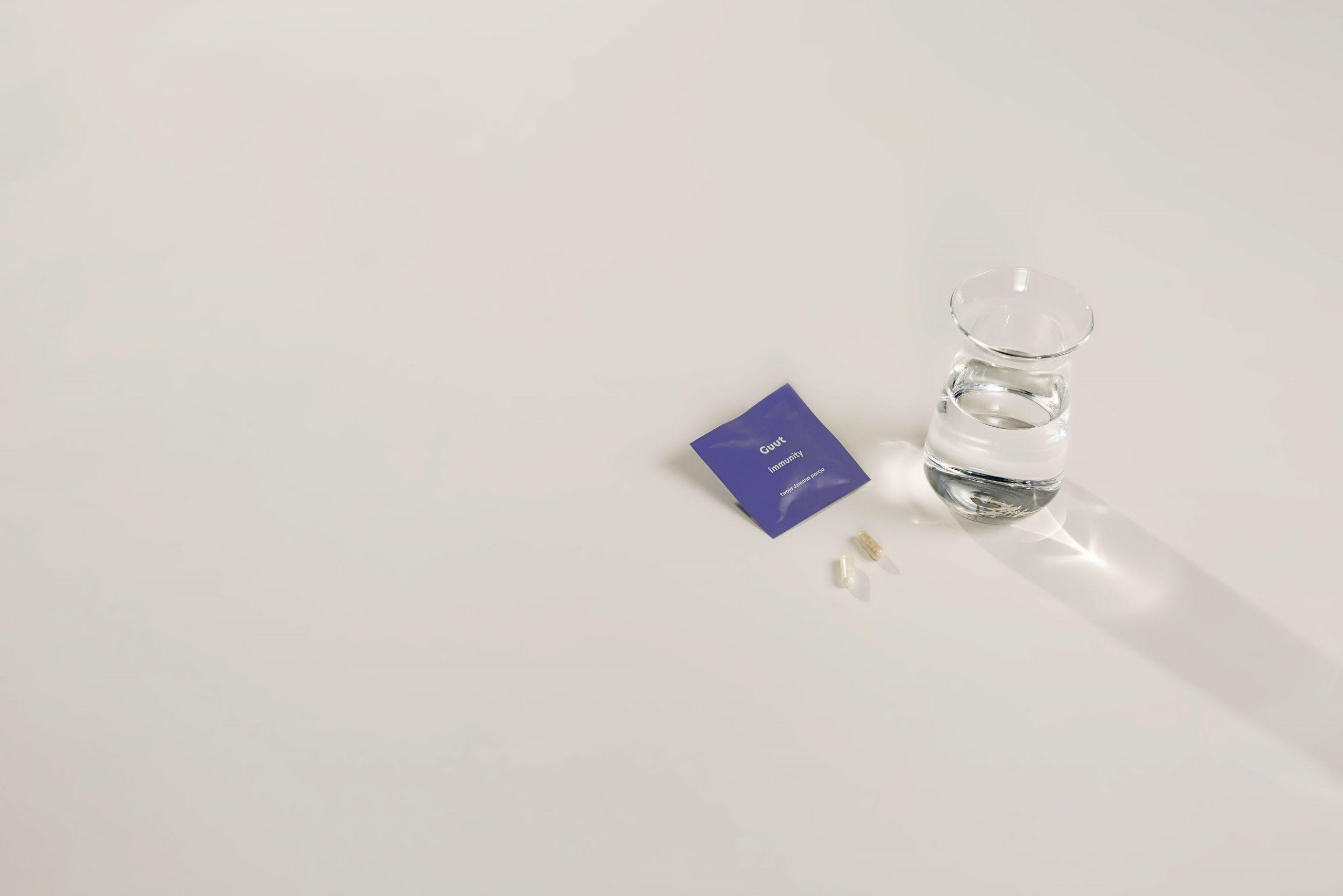 """tło sekcji """"funkcje"""" Guut Immunity -zdjęcie saszetki, szklanki wody i kapsułek"""