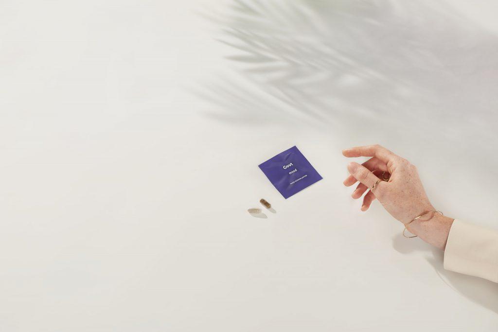 tło sekcji Funkcje Guut Mood - zdjęcie saszetki, kapsułki i dłoni