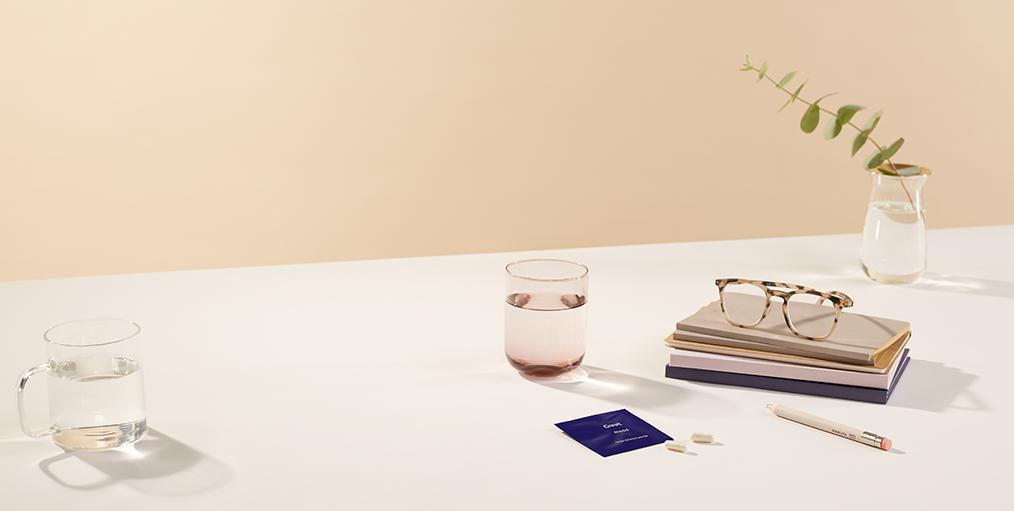 saszetka Guut leżąca na stole, obok szklanki wody i książki